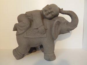 Kindmonnik op olifant. Hoogte 57 cm. Granite kleur